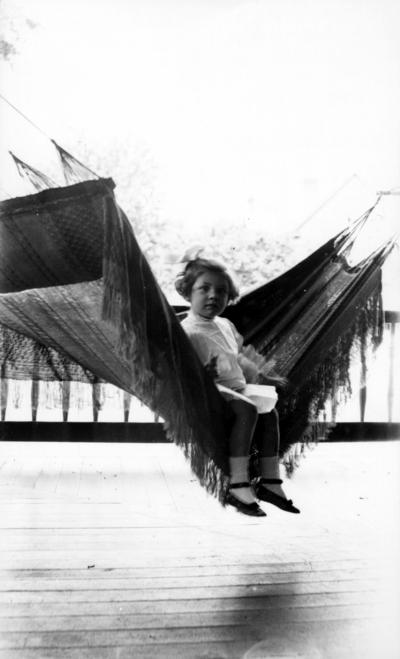 Little girl seated in hammock