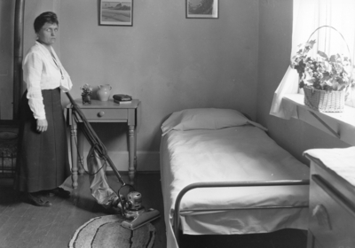 Interior of bedroom, woman with vacuum