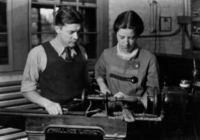 Woman using a lathe as instructor watches