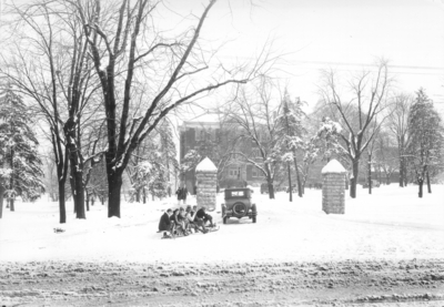Entrance to the University of Kentucky with a car pulling students on a sled toward Frazee Hall