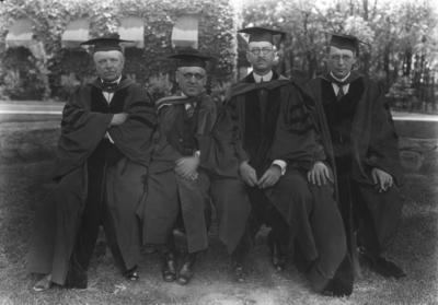 Four men seated, Dean F. Paul Anderson on left, Richard Stoll, Board of Trustees, on right