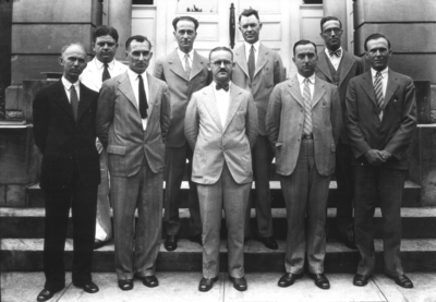 Group photograph on steps of Frazee Hall, connected with high school extension teachers, includes Kenneth Harding, Snapp