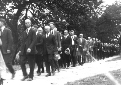 Students in procession, several with heads shaved