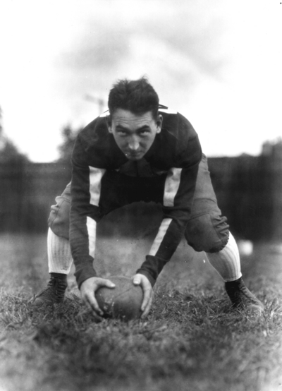 Kentucky football player in position to snap the ball