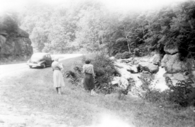 Two unidentified women standing on edge of road, looking a waterfall, mountain scene