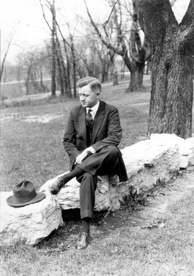 Unidentified man seated on stone wall