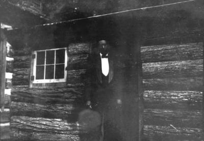 Unidentified African American man in door of log cabin