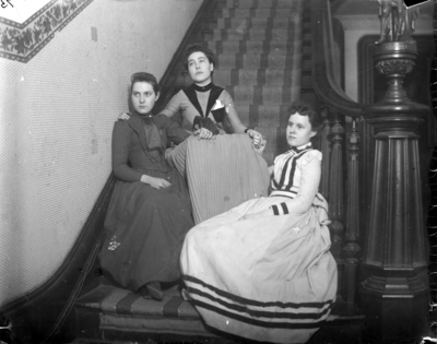 3 women sitting at the foot of the stairs