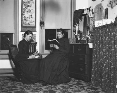 2 women sitting together inside, possibly a dorm room in Patterson Hall (built in 1904) the first women's dormitory
