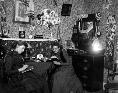 2 women sitting at a table, possibly in a dorm room in Patterson Hall,  reading and writing