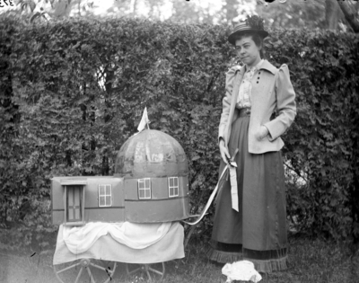woman standing with a model of an observatory on a small cart