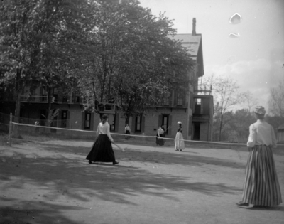 women playing tennis, possibly behind Patterson Hall on land that is now occupied by Blazer Hall