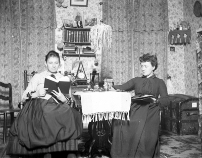 2 women, one is reading and the other is working at a table