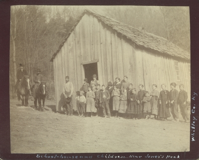 Unidentified adults and children in front of a school house near Jones Peak in Whitley County, Kentucky
