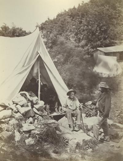 Unidentified men around a tent. Caption reads