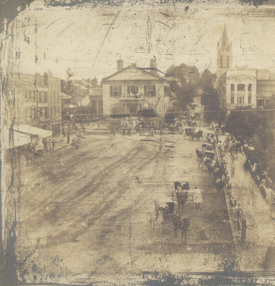 Cheapside, Lexington, KY with several horse carriages near courthouse