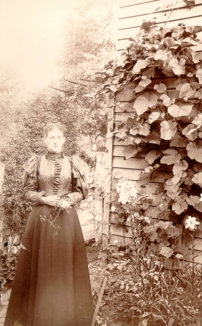 Helen Lyle standing in garden next to house; variant of #198