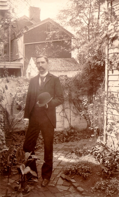 Charles Nourse Lyle standing in garden holding his hat