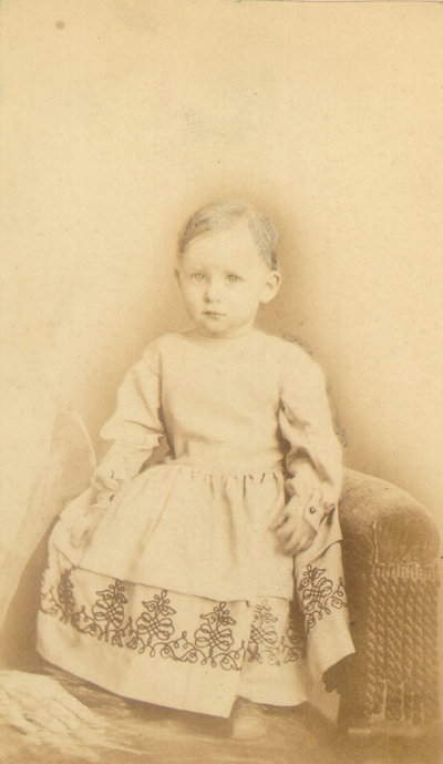 Baby in white dress with hair partially drawn in