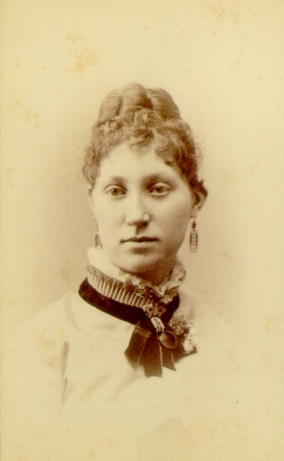Young woman with done up hair wearing white blouse