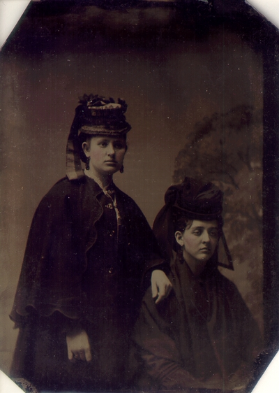 Young woman standing next to seated Lizzie Lyle; Both dressed in full dark outfitted; Quote to left of photo reads