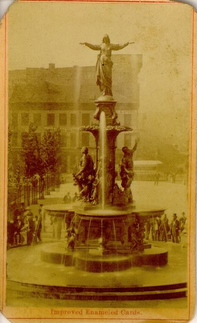 Large fountain with people standing at the base of it; Fountain has clover-like bowls with statues at top