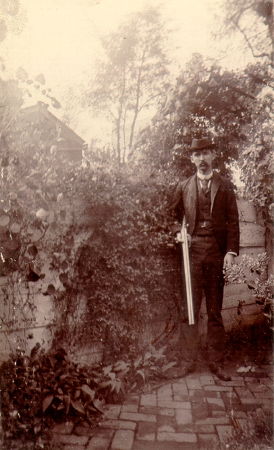 Charles N. Lyle standing in garden in front of fence holding a shotgun