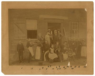 Twenty men and women standing in front of building, handwritten on back in ink                              Laboratory / at Annisquam / Mass. - / Summer of / 1886. / Photo by / Jacob Reighard (l to r)                              1. Elmer Hodgkins - Annisquam / 2. J.H. Morgan - Lexington, Ky / 3. K.E. Farrand - Detroit, Mich. / 4. Edith Guild - Boston / 5. B.P. Colton - Ottawa, Ill. / 6. Ellen Folger - Concord, N.H. / 7. May Murray - New York, N.Y. / 8. Chas. Farr - New Castle, Ind. / 9. Fanny Julian - New York City, N.Y. / 10. Alma S. Bingham - Jamaica Plain, Mass. / 11. C.P. Shoemaker Philadelphia, Pa. / 12. J.E. Reighard - La Porte, Ind. / 13. Linda E. Horns - Detroit, Mich. / 14. H. G. White - Farmington, Mass. / 15. Lemine Martin - Boston / 16. Anna Shoemaker - Philadelphia, Pa. / 17. Robert Wood - Jamaica Plain, Mass. / 18. Henry Ward - Troy, N.Y. / 19. Arthur Biffins - Albion, Mich. / 20. Evelyn Borrow - Reading, Mass