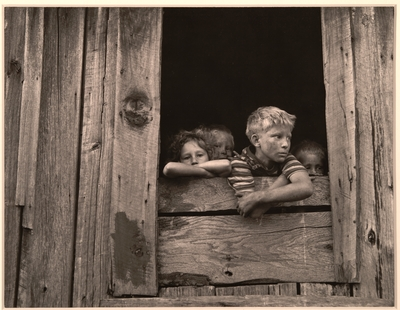 Children of miners look out the kitchen window of the Monroe Jones house.  The windows have no panes, the door frames have no doors; old quilts and boxes are used during the winter for protection.  Four Mile, Bell County, KY. 9/4/46
