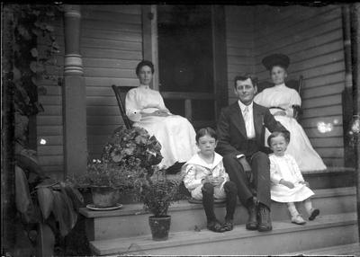 Family sitting on a porch;                          Adams Negative handwritten on envelope