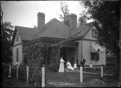 Family in front of a house;                          Adams Negative handwritten on envelope
