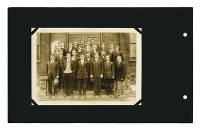 Group portrait: male students and professor on steps of building
