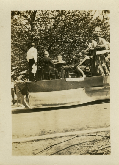 Men and women seated on a May Day float May 2, 1930