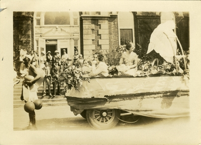 Women on a parade float with spectators in the background May 2, 1930