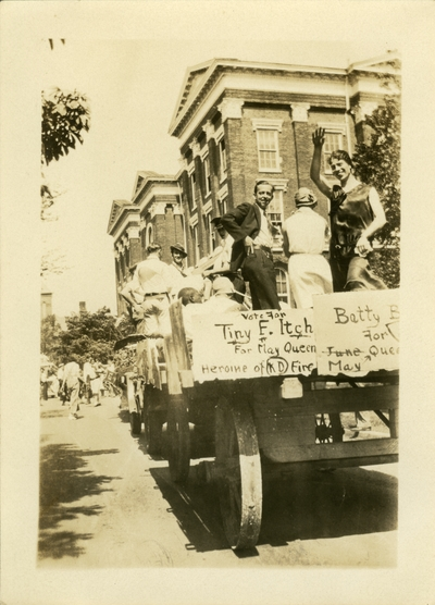 Men and women on a wagon float as part of a parade.  Sign on float reads