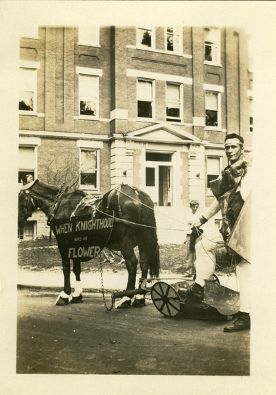 May 1930 A man dressed in costume with a horse wearing a sign: