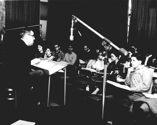 A professor speaking to students in a studio classroom;