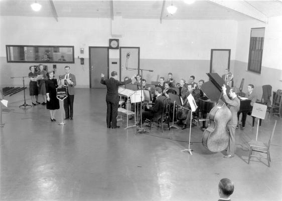 UK Radio Studios: Band being conducted while two sets of people stand at microphones (Mutual Broadcasting system banner hanging on first microphone)