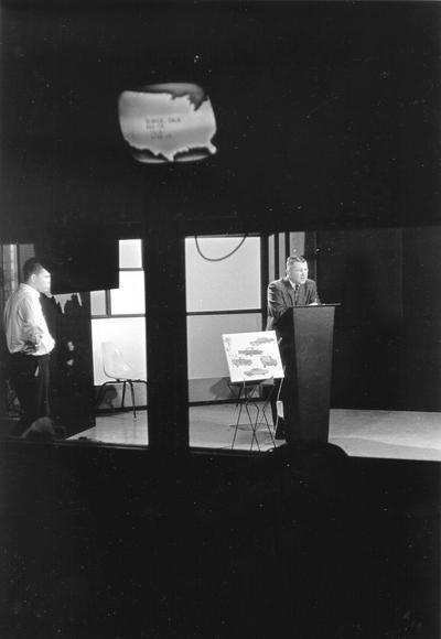 Man at a lectern in studio (Dr. Ellis Hartford)