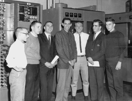 Seven young men standing in engineering department of radio or television station (Tom Jordan, Dick Lowe, Wayne Gregory, Jimmy Allison)