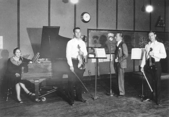 Musicians (one woman, two men) and announcer at WHAS/UK studio: group preparing to perform