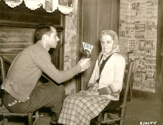 Young man holding CBS microphone head to show elderly woman