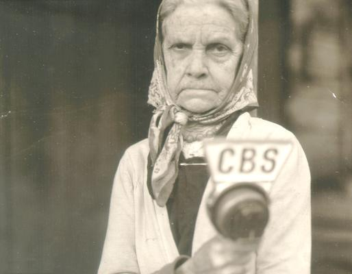 Same elderly woman as in #563, holding CBS microphone