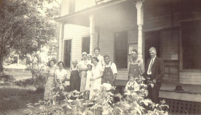 Group of people standing together for photograph outside of building
