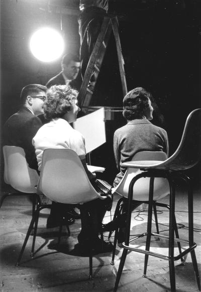 Three persons sitting in TV studio