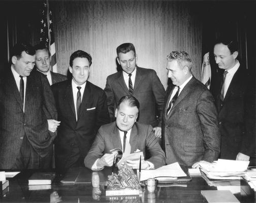 Kentucky Governor Bert T. Combs sitting at desk, future Governor Louie B. Nunn in black suit looking at camera, Len Press at far right (Frankfort, KY) (L to R: Bill Small, WHAS News Director; Ron Stewart, WBKY Chief Engineer; Harry King Lowman, Speaker of the House; Townes Ray, Majority Leader of the House; Wendell Butler, press)