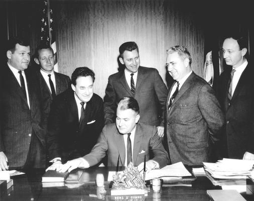 Kentucky Governor Bert T. Combs at desk, future Governor Louie B. Nunn leaning over, Len Press at far right, 4 unidentified men; Frankfort, KY (L to R: Bill Small, WHAS News Director; Ron Stewart, WBKY Chief Engineer; Harry King Lowman, Speaker of the House; Townes Ray, Majority Leader of the House; Wendell Butler, press)