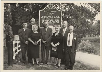 A group of five men and three women standing in front of a plaque (August 13, 1961):                          Hazel Green Academy / Dedicated 1800 by J. Taylor Day, William D. Mize and Green Berry Swango. Only College Preparatory School This Area ForYears