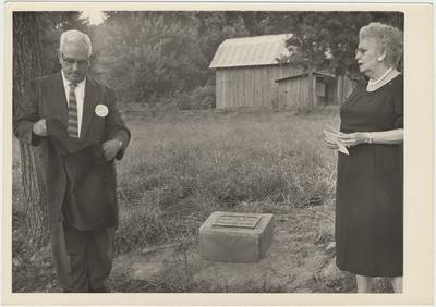Man and woman standing near a marker on the ground (August 13, 1961). Pearl Day (Mrs. Wm. Everett) Bach is on the left. HGA Director, Mr. Henry A. Stovall, is on the back row, far right