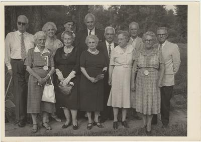 Group of seven women and five men standing on a lawn (August 13, 1961). On the right is Former Students Association historian, Mrs. Pearl Day Bach